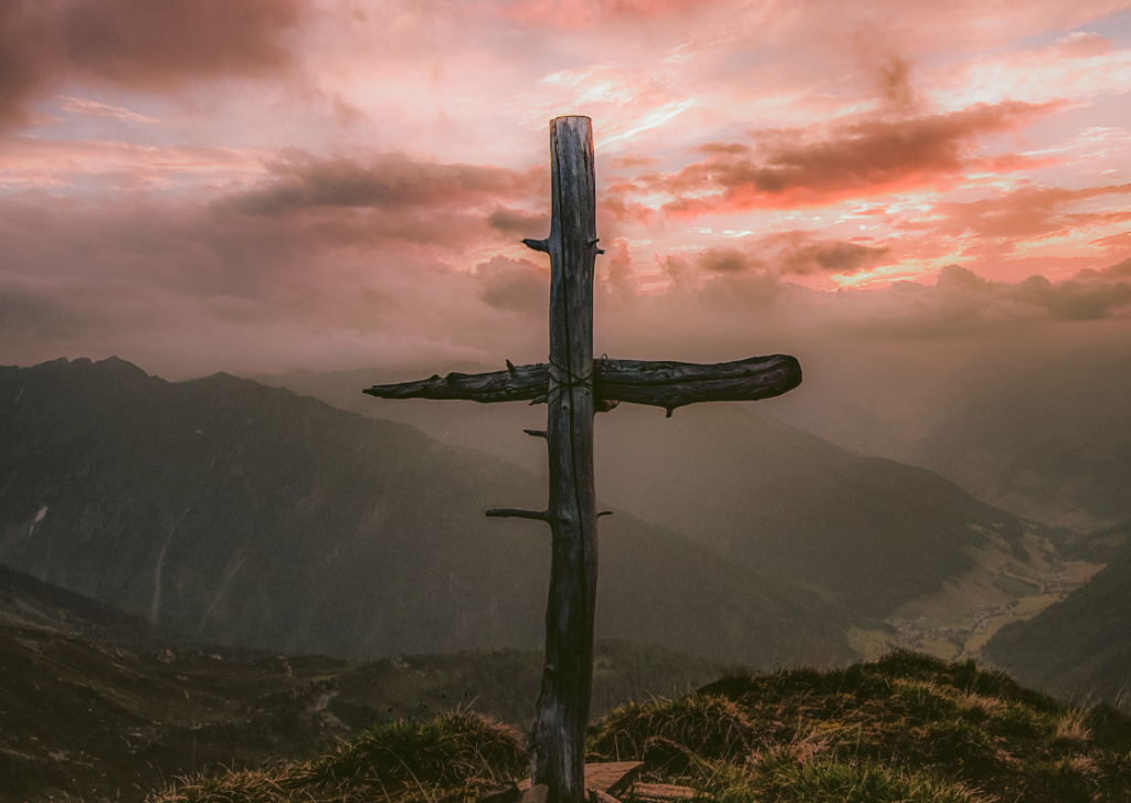 A photo of a cross on a hill.