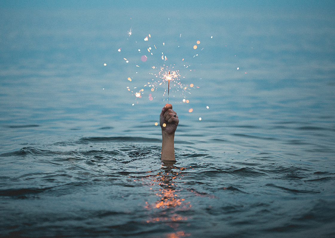 A photo of someone holding a sparkler above water